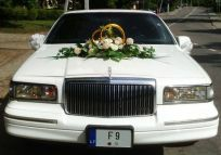 Lincoln limousine in front of photos from the wedding. The model manufactured from 1995 to 1997